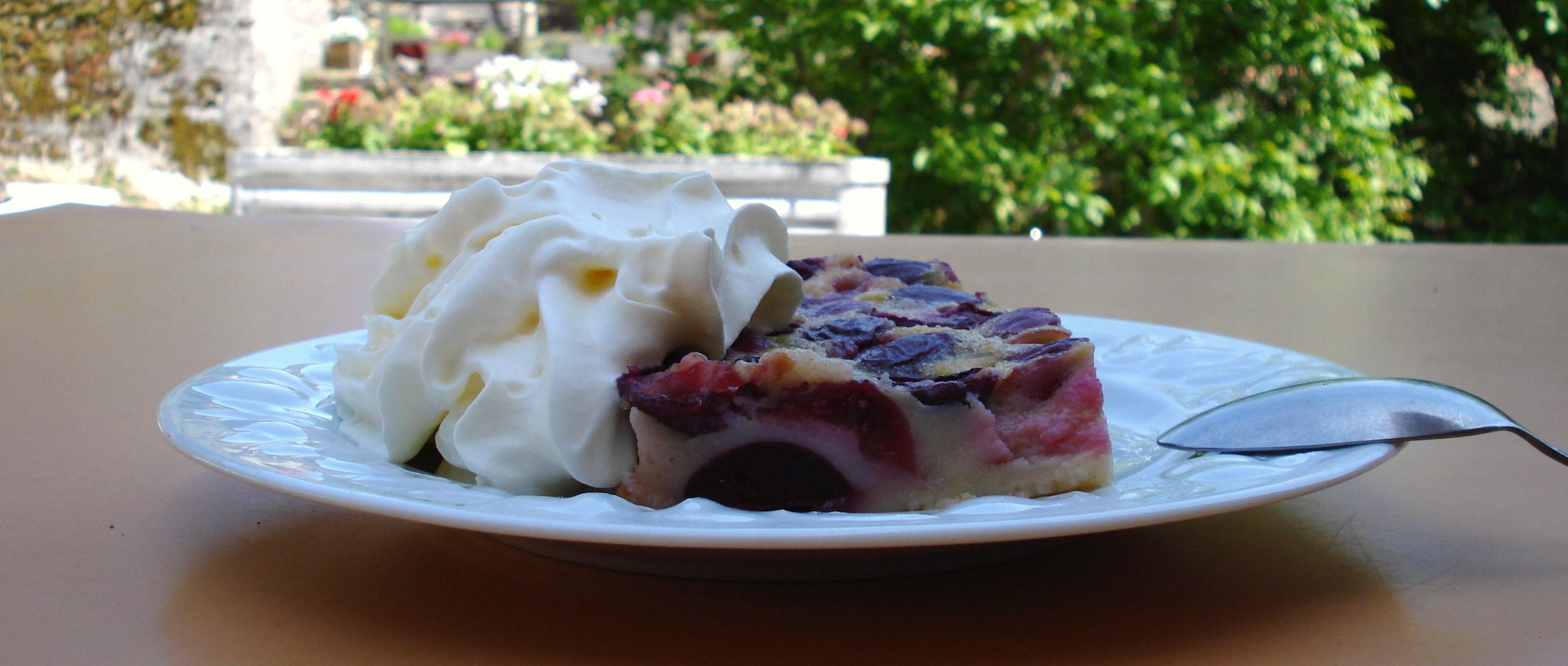 Une délicieuse part de clafoutis avec de la crème fouettée.