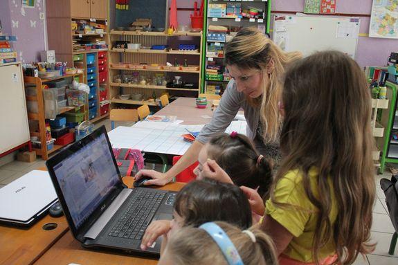 Maîtresse et élèves devant le blogue de l'Ecole
